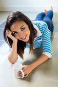 Beautiful brunette girl who is lying on the floor and drinking c — Stock Photo
