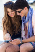 Young couple having fun with smartphones, outdoors — Stockfoto