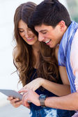 Happy young couple browsing internet with digital tablet  in the — Stock Photo