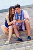 Young couple having fun with smartphones, outdoors — Stock Photo