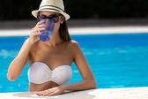 Mooi meisje drinkwater bij het zwembad. — Stockfoto