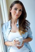 Beautiful woman drinking coffee in the morning near the window. — Stock Photo