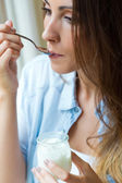 Young woman at home eating yogurt  — Stock Photo