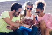 Skupina studentů při pohledu na knihu v ulici. — Stock fotografie