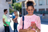 Beautiful student girl using her mobile phone in the street.  — Stock Photo