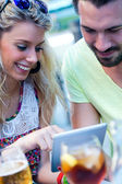 Couple of young students using a digital tablet in the bar.  — Stock Photo