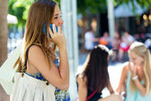 Beautiful young girl talking on mobile phone in the street.  — Foto Stock