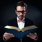 Intrigued businessman with glasses reading a book. Isolated on black. — Stock Photo