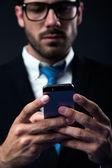 Handsome stylish man in elegant black suit using mobile phone. — Stock Photo