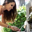 Beautiful woman drinks water from source in summer city park.  — Stock Photo #50534681