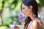 Young beautiful girl smells flowers, against green summer garden — Stock Photo