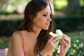 Young beautiful woman eating piece of melon in the garden.  — Stock Photo