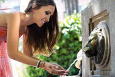 Beautiful woman drinks water from source in summer city park.  — Stock Photo