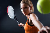Beautiful woman playing tennis indoor. Isolated on black. — Foto de Stock