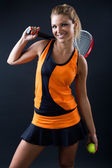 Sporty teen girl tennis player with racket. Isolated on black. — Stock Photo