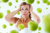 Young girl overwhelmed by diet, surrounded by apples. — Foto Stock