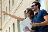 Young tourist couple use their map and pointing where they want  — Stok fotoğraf