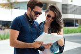 Young tourist couple in town holding a map. — Stock Photo