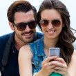 Young couple of tourist in town using mobile phone. — Stock Photo #50930681
