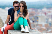 Young couple of tourist in town using mobile phone.  — Stock Photo