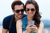 Young couple of tourist in town using mobile phone.  — Foto de Stock