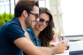 Happy couple of tourist in town using mobile phone.  — Stock Photo