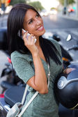 Beautiful girl sitting on a scooter and talking with phone. — Foto de Stock
