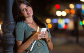 Beautiful woman use her phone in the city at night. — Stock Photo