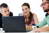 Casual executives working together at a meeting with laptop. — Stock Photo