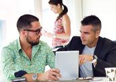 Casual executives working together at a meeting with digital tab — Stock Photo