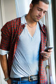 Elegant young handsome man with mobile phone. — Stock Photo