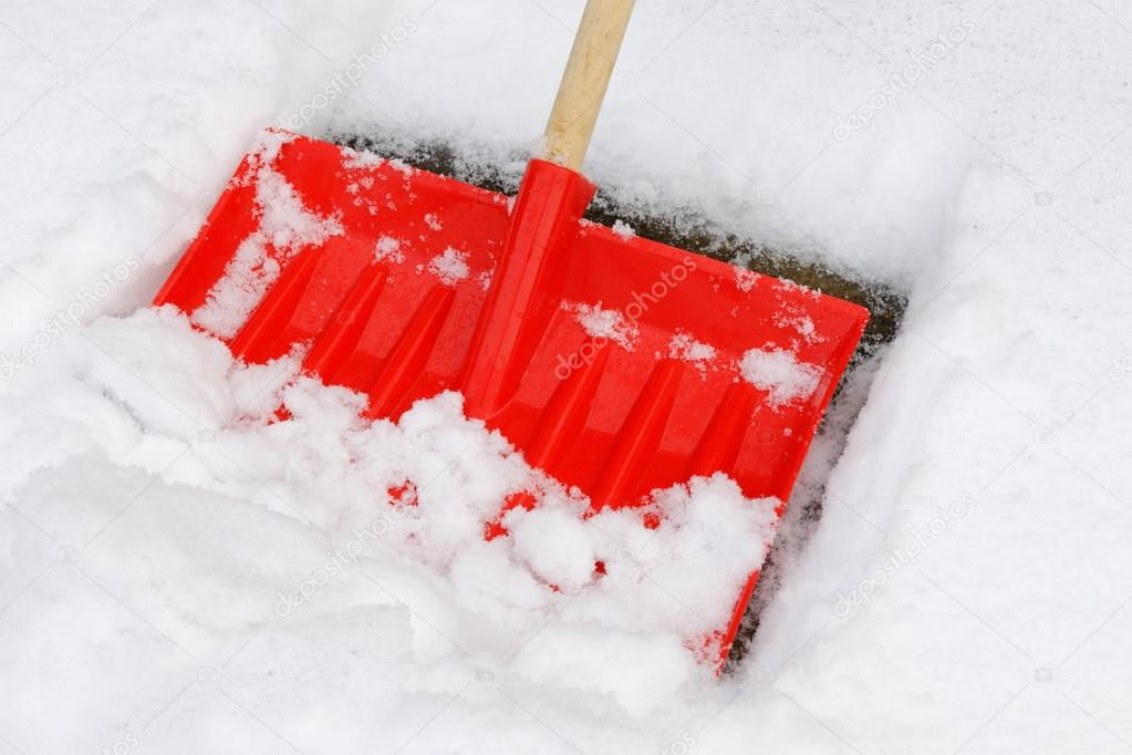 A snow shovel being used to clear a pavement - close up  Stock Photo #19129443