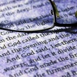 Stock Photo: Reading glasses on bible text