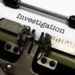 Stock Photo: Investigation text on typewriter