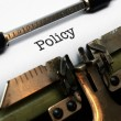 Policy on typewriter — Stockfoto