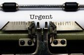 Urgent text on typewriter — Stock Photo