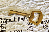 Publish and golden key — Stock Photo