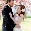 Bridal Couple Showered by Cherry Blossom Petals - Stock Photo