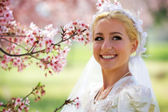 Bride Smiles Next to Cherry Blossom Tree — Stock Photo