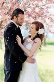 Bridal Couple Showered by Cherry Blossom Petals — Stock Photo