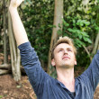 Stockfoto: Mraises arms above his head