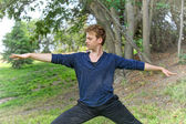 Man Performs Yoga Warrior Pose in Park — Stock Photo