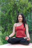 Woman Sits in Yoga Lotus Pose on park table — Stock Photo
