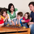 Stock Photo: Family is playing an board game