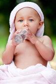Baby en een olie-fles — Stockfoto