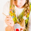 Young girl painting eggs for easter - Stock Photo