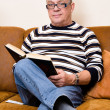 Senior reading his book on the couch — Stock Photo