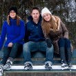 Trio sitting on a parkbench in winter — Stock Photo