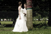 Groom and bride playing hide and seek with a totem — Stock Photo