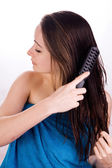 Woman is grooming her hair — Stock Photo